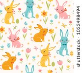 Stock vector cute easter seamless pattern of multicolored bunnies easter eggs spring flowers butterflies and 1022498494
