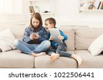 two kids with gadgets. sister... | Shutterstock . vector #1022506441