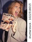 Small photo of Los Angeles, California - exact date unknown - circa 1990: Former Playmate and wife of Gene Simmons, Shannon Tweed holding issue of Playboy with her on the cover and making a funny face