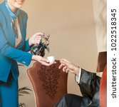waitress serving arabic coffee... | Shutterstock . vector #1022518345