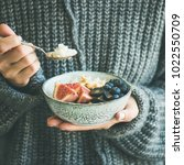 healthy winter breakfast. woman ... | Shutterstock . vector #1022550709