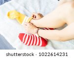 Small photo of The girl sit on a white carpet and put on socks, yellow punctuate red side.