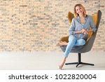 young woman sitting in armchair ... | Shutterstock . vector #1022820004