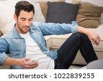young man sending a message... | Shutterstock . vector #1022839255