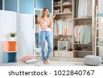 young woman choosing clothes in ... | Shutterstock . vector #1022840767