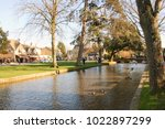 The quaint Cotswold village of Bourton on the Water, Gloucestershire, UK, with the brook running down the high street