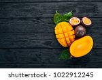 Small photo of Mango and passion fruit. Fresh Tropical Fruits. On a wooden background. Top view. Copy space.