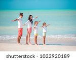 happy family on a beach during... | Shutterstock . vector #1022920189