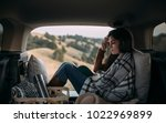 Small photo of Woman vacationer enjoying picnic in car trunk and reading.