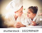 Small photo of Portrait of beautiful mother and daughter looking etch other.