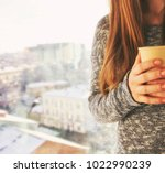 the young woman holds cup of... | Shutterstock . vector #1022990239