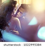 loving couple posing in bedroom.... | Shutterstock . vector #1022995384