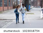 Young Woman Helping Blind Man...