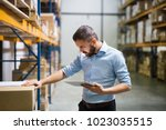 man warehouse worker with a... | Shutterstock . vector #1023035515