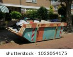 loaded dumpster near a... | Shutterstock . vector #1023054175