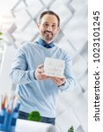 Small photo of Good job. Good-looking alert dark-haired bearded man smiling and holding a model of a future house while standing at the table