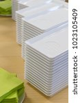 a stack of white plastic plates