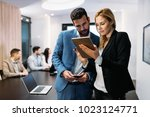 businesspeople discussing while ... | Shutterstock . vector #1023124771