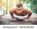 young sportsman doing push up... | Shutterstock . vector #1023146365