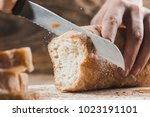 Whole grain bread put on kitchen wood plate with a chef holding gold knife for cut. Fresh bread on table close-up. Fresh bread on the kitchen table The healthy eating and traditional bakery concept