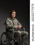 Small photo of Portrait of hopeful handicapped young veteran sitting in invalid chair. He is looking up with belief and his hands folded in the lock. Concept of hope. Isolated on grey background