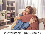 Small photo of Happy young female embracing mother while locating in living room. Cuddle concept