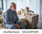 upset old man sitting on bed... | Shutterstock . vector #1023289285