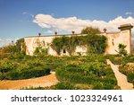 flowerbeds and a wall overgrown ... | Shutterstock . vector #1023324961
