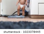 a baby boy is cleaning the room.... | Shutterstock . vector #1023378445