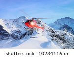 red helicopter flying in swiss... | Shutterstock . vector #1023411655
