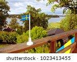 swedish flag in a garden.... | Shutterstock . vector #1023413455
