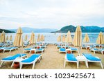 sun loungers on a beach in... | Shutterstock . vector #1023425671