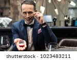 Small photo of handsome man in stylish suit making propose in restaurant
