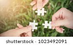 hands trying to connect puzzle... | Shutterstock . vector #1023492091