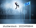 businessman jumping over tax in ... | Shutterstock . vector #1023498844