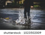 child jumping in a puddle on a...   Shutterstock . vector #1023502009