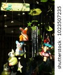 Small photo of Many clay dolls and ornaments with light and shadow in home decorations concept ,Thai language in wooden lable is mean so happy and so much money