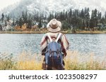 Adventure woman feeling happy among amazing mountains, enjoy the nature landsape. Forest and lake, wearing backpack, hat and poncho, boho and wanderlust style