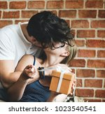 wife receives a gift box from... | Shutterstock . vector #1023540541