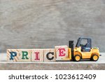 Small photo of Toy forklift hold letter block E to complete word price on wood background