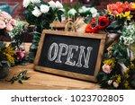 open sign among flowers bouquet ...   Shutterstock . vector #1023702805