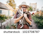 Stock photo happpy young bearded farmer holding two little kitten in hands outdoor in village with abstract 1023708787