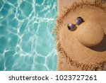 straw hat on the edge of the... | Shutterstock . vector #1023727261
