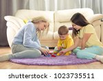 child plays in designer. mom... | Shutterstock . vector #1023735511