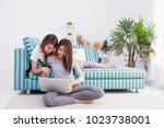 two asia woman using laptop... | Shutterstock . vector #1023738001