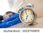 awaked man looks at the alarm... | Shutterstock . vector #1023744895