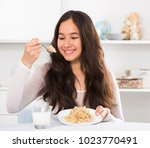 Young Smiling Girl Eating Tast...