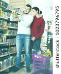 Small photo of Young glad pleasant couple standing near shelves with canned goods at store