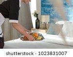 Stock photo room service woman bringing breakfast on a tray to a guest s hotel bed 1023831007