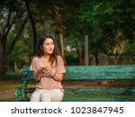 young asian woman sitting on... | Shutterstock . vector #1023847945